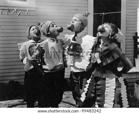 Kids biting apples on strings at Halloween - stock photo