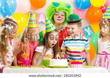 kids blowing candle on festive cake - stock photo