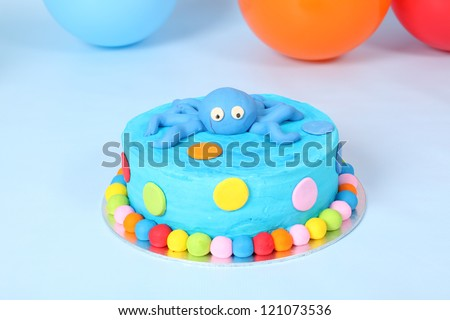 Kids blue round birthday party cake with red, yellow, blue and pink polka dots and cute blue fondant octopus on top. All on blue background with balloons and flag bunting.