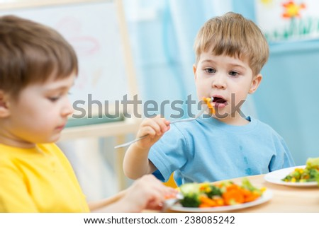 kids boys eating healthy food in kindergarten or at home - stock photo