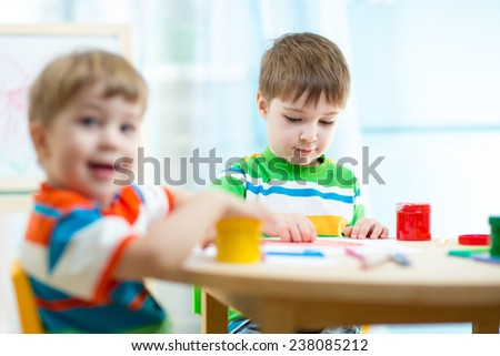kids boys painting in daycare or nursery or playschool - stock photo