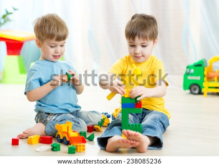 Kids boys play toys in playroom at nursery - stock photo