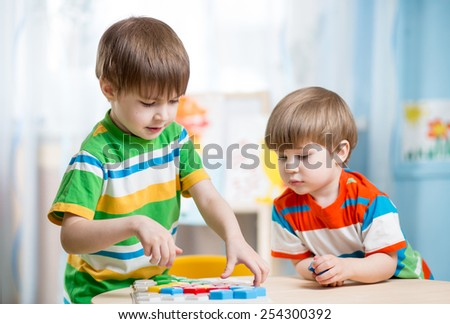 kids boys playing toys together at table - stock photo