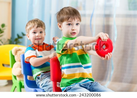 Kids boys riding on carriages made from chairs - stock photo