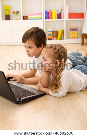 Kids busy and concentrated working on a laptop laying on the floor in their room - stock photo