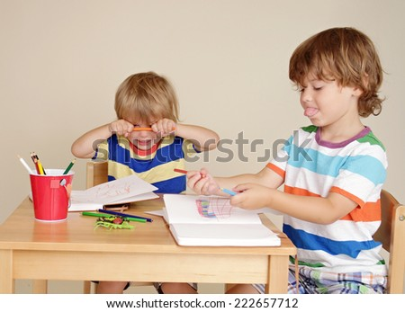 Kids, children engaged in art and craft with pencils and paper, being silly and making faces - stock photo