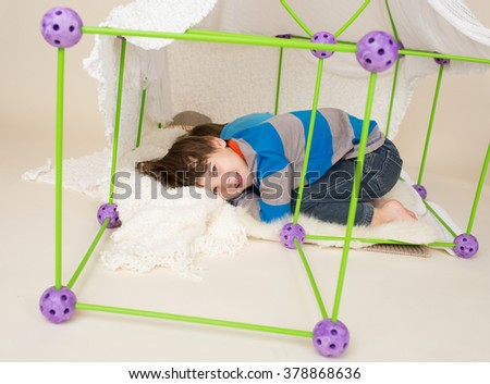 Kids, children, playing with a tent or fort made out of blankets, imagination, pretend play concept