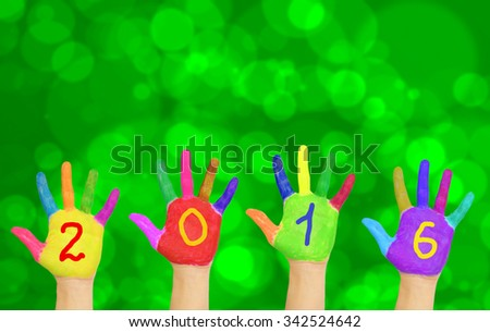 Kids colorful hands forming number 2016 against New Year blurred bokeh green background.  - stock photo