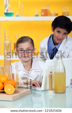 Kids conducting an experiment on oranges - stock photo