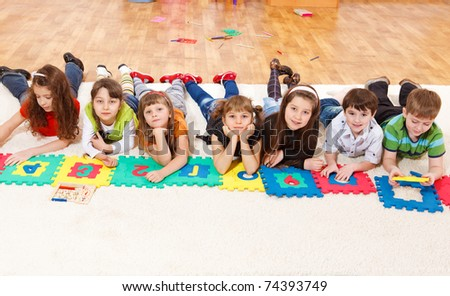 Kids crowd lying in line - stock photo