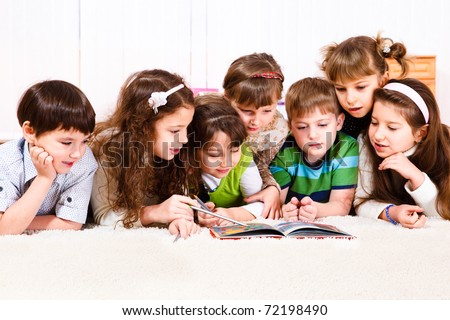 Kids crowd reading a book - stock photo