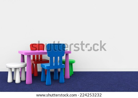 Kids desk and chairs against a blank wall - stock photo