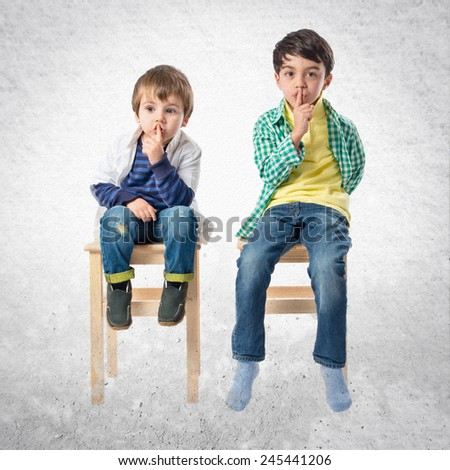Kids doing silence gesture over textured background  - stock photo