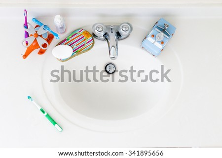 Kids Domestic Bathroom Sink with toothbrushes and hand soap - stock photo