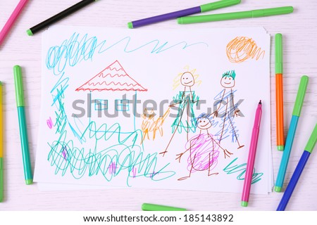 Kids drawing of family and colored pencils on wooden table - stock photo
