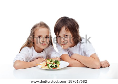 Kids eating a decorated spaghetti dish - isolated - stock photo