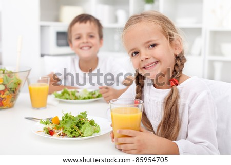 Kids eating a healthy meal in the kitchen - stock photo