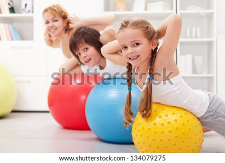 Kids exercising with their mother at home