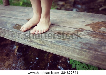 Kids feet standing on the wooden bridge in mountain creek - stock photo