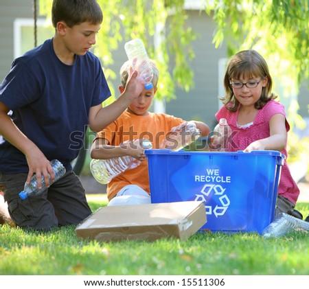 Kids filling recycle bin - stock photo