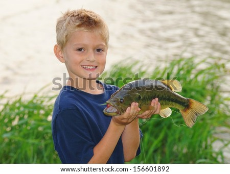 Kids fishing - a cute boy smiles as he holds a big fish he caught - stock photo