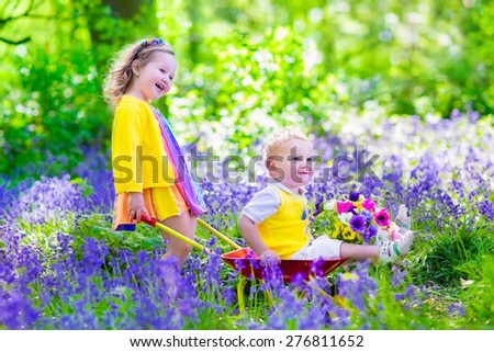 Kids gardening. Children playing outdoors. Little girl and baby boy, brother and sister, working in the garden, planting flowers, watering flower bed. Child pushing wheel barrow. - stock photo