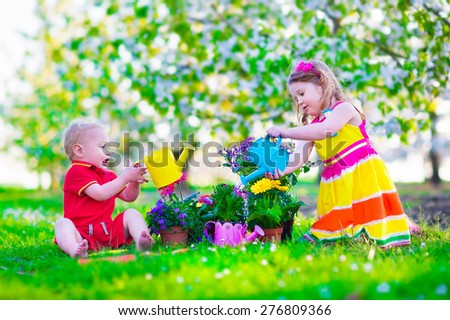 Kids gardening. Children playing outdoors. Little girl and baby boy working in the garden, planting flowers, watering flower bed. Family in blooming fruit tree orchard. Summer vacation on a farm. - stock photo