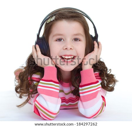 Kids,girl,kid,child- charming and very musical little girl is listening to music. Isolated on white background. - stock photo