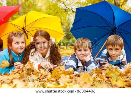 Kids group hiding under colorful umbrellas - stock photo