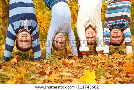 Kids group upside down in an autumn park - stock photo
