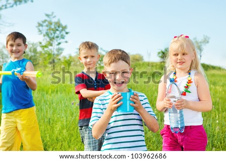 Kids group with toy water guns and other water containers - stock photo