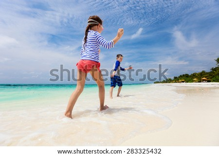 Kids having fun at tropical beach during summer vacation - stock photo