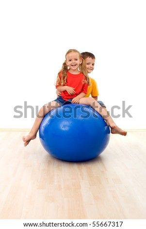 Kids having fun making exercises with a large gymnastic rubber ball - partially isolated - stock photo