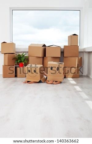 Kids having fun while moving in a new home - laying with cardboard boxes - stock photo