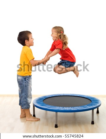 Kids having fun with a trampoline in the gym - isolated, slight motion blur
