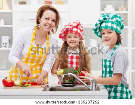 Kids helping mother preparing a salad in the kitchen - washing the vegetables