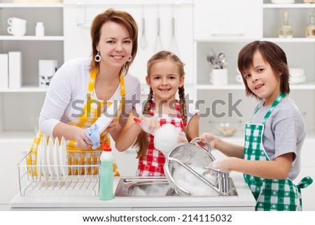 Kids helping their mother in the kitchen - washing the dishes - stock photo