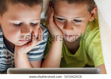 Kids hiding under blanket and holding tablet - stock photo