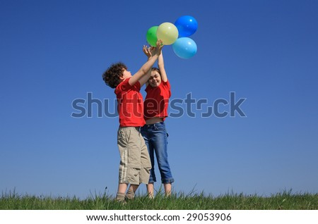 Kids holding balloons playing outdoor - stock photo