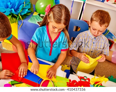 Kids holding colored paper on table in kindergarten . - stock photo
