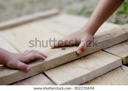 Kids holding hands on wooden board in workshop - stock photo