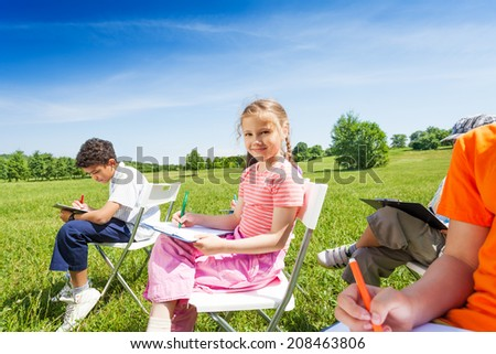 Kids holding sketch-boards and sit on chairs