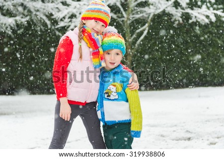 Kids in colorful clothes playing in the park under snowfall, wearing colorful knitwear. - stock photo