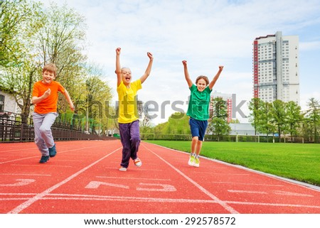 Kids in colorful uniforms with arms up running - stock photo