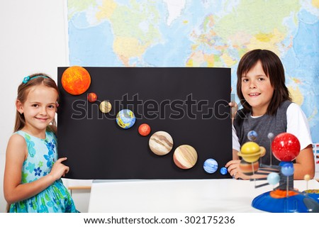 Kids in elementary school science class study the solar system - making a scale model of the planets - stock photo