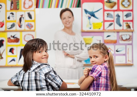 Kids in elementary science class with their teacher - focus on the boy - stock photo