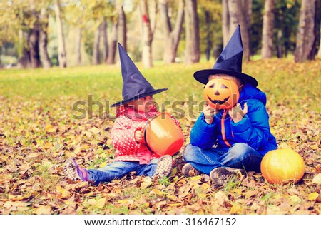 kids in halloween costume play at autumn park, kids trick or treating - stock photo
