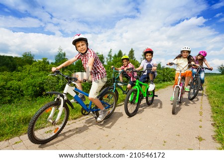 Kids in helmets riding bikes together - stock photo