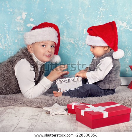Kids in red santa hat with their christmas presents presents sitting and lying on the floor