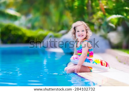 Kids in swimming pool. Children swim outdoors. Toddler child during vacation in a tropical resort with palm trees. Little girl playing on a beach. Active kid in summer with colorful toy floating ring. - stock photo
